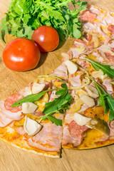 Pizza with salami, mozzarella, mushrooms, ruccola and tomato