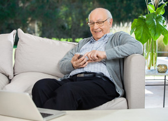 Happy Senior Man Text Messaging Through Smartphone At Porch