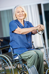 Smiling Senior Woman Sitting On Wheelchair At Yard