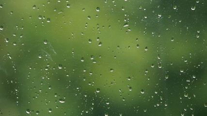 Close up of a window with rain drops falling down