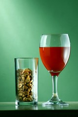 goblet of red wine and a glass of peanuts