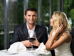 Cheerful couple in a restaurant with glasses of red wine