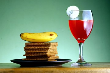 Stack of crackers, banana, fruit juice with cucumber slices