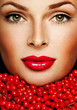 beautiful woman's face surrounded by red berries