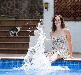 Girl in dress resting near pool
