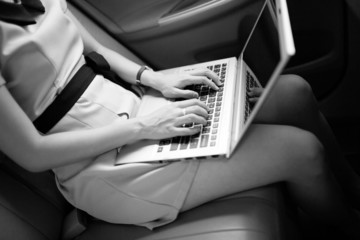 businesswoman with document and laptop in car