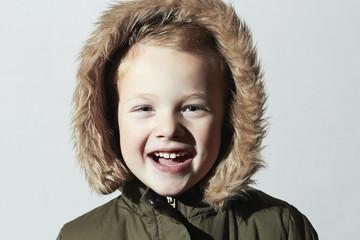 Smiling child in fur hood.fashion kids.parka.little boy winter