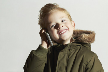 smiling little boy talking on the cellphone. happy child.winter
