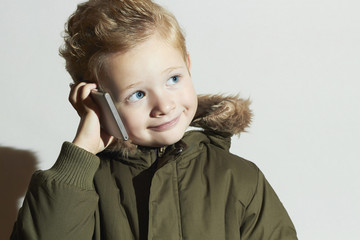 funny little boy talking on the cellphone.winter fashion kids