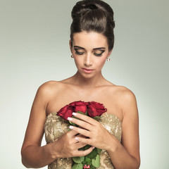 young elegant woman looking down at red roses