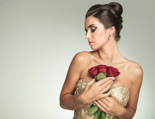woman holding roses to her chest and looks to side
