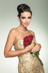 young beautiful woman in golden dress holding red roses