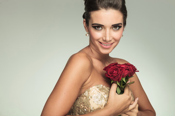 elegant woman in dress smiling while holding red roses