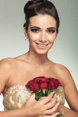 woman holding red rose flowers to her chest and laughs