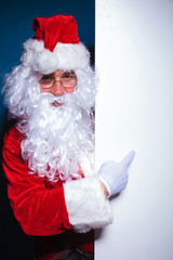 Santa claus pointing to a blank board