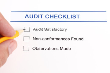 Audit checklist and human hand with pencil