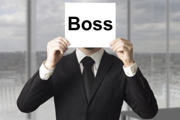 businessman hiding face behind sign boss
