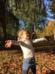 Mädchen spielt im Laub