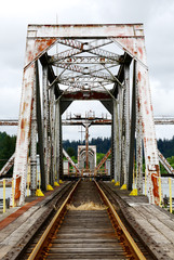 Large steel pivot railroad bridge spanning the Umpqua River bay