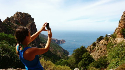 Woman taking picture of beautiful view in the sea