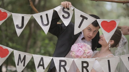 Newlyweds having fun in the park decorated with letters and