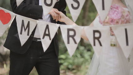 Newlyweds kissing in a park decorated with letters and words
