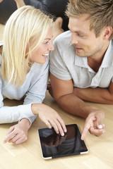 Mid adult couple lying on floor using tablet