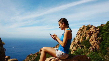 Woman texting a message in the mountains