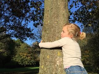 Mädchen umarmt einen Baum