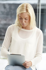 Mid adult woman in white top using tablet