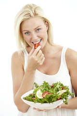 Mid adult woman eating from salad bowl, portrait