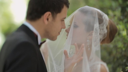 Fiance kisses the bride through the veil