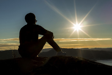 Silhouette man on a mountain enjoying the view at sunset