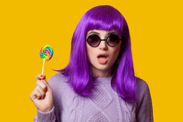 Surprised girl with violet hair on violet background.