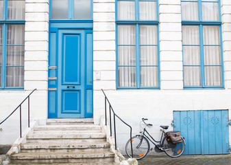 A bicycle parked near the facade of white building