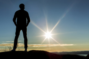 Silhouette male standing on a mountain looking at the sunset
