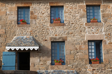 Old stone building with blue windows and red flowers