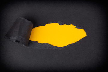 Yellow paper background appearing behind torn black paper