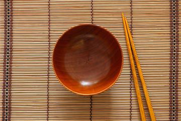 Empty wooden bowl and chopsticks