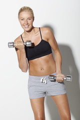 Mid adult woman lifting weights, portrait