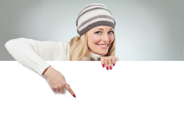 Blond woman holding blank banner. Winter theme. Studio shot.