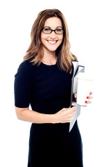 Businesswoman holding folders and hot drink