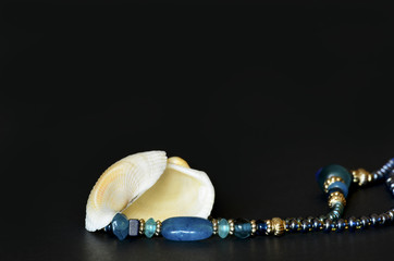 Seashell with blue pearls isolated on black background