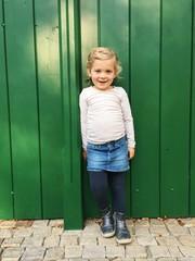 Junges Mädchen steht an grüner Wand