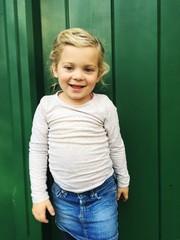 Mädchen steht vor grüner Tür