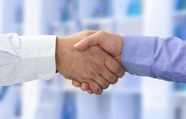 Hände beim Vertragsabschluss vor blau