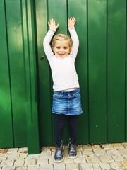 Mädchen vor grüner Tür macht Arme hoch