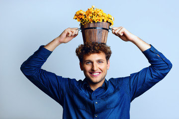 Smiling man with a bucket on his head with flowers