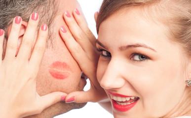 Woman framing lipstick kiss on a man face.