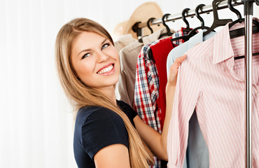 Smiling female shopper choosing shirt at clothing rack